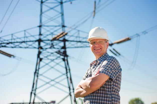 送電線の下に白いヘルメットを持つ経験豊富なエンジニア。