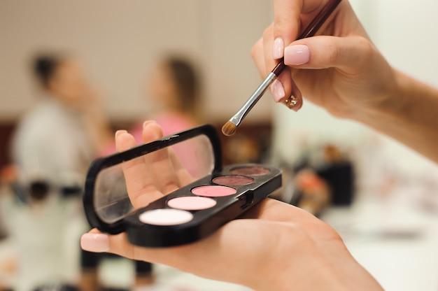 Кисти для макияжа, изделия в руках, фото крупным планом