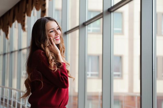 空港で電話で話している若い女性