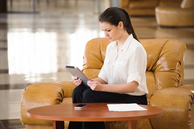 ソファーに座りながら働く忙しいビジネスの女性の肖像画
