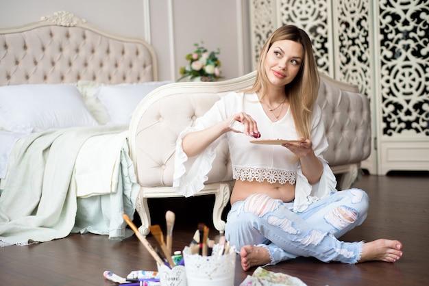 妊娠中の若い女性アーティストは彼女のワークショップで油絵の具でキャンバスに絵を描く