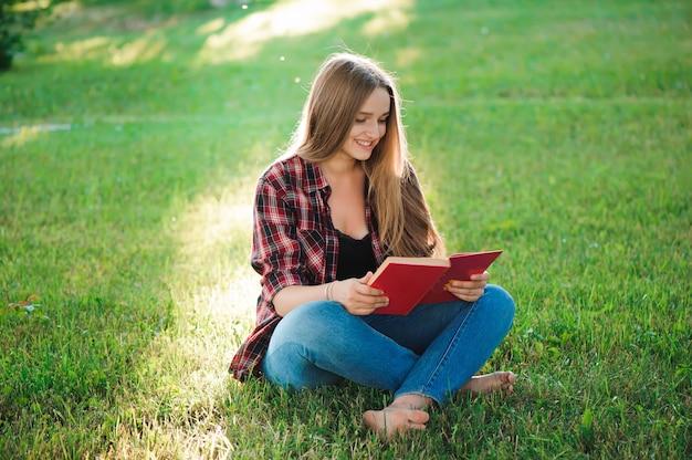公園で本を読んでかなり金髪の若い女性