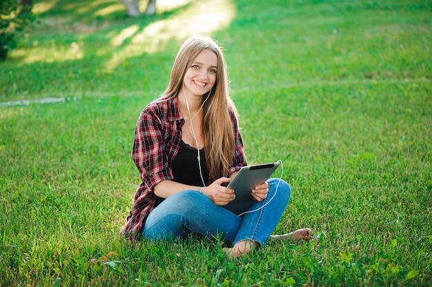 Счастливая девушка хипстер с помощью планшета на открытом воздухе в парке