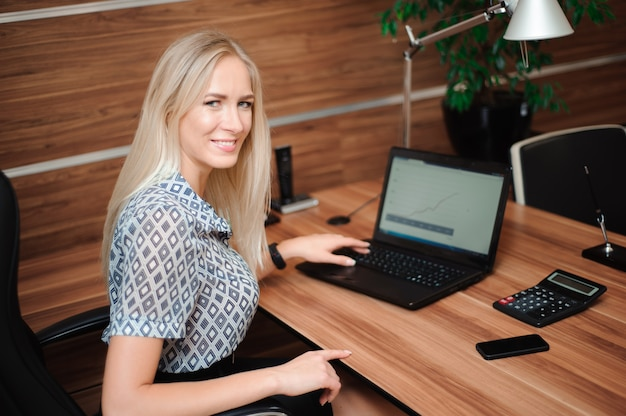 Красивая деловая женщина работает с продажами в ее офисе