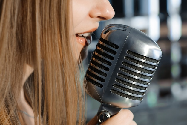 Певица перед микрофоном караоке-клуба.