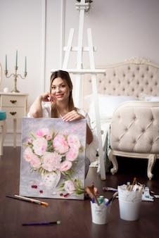 女性アーティストが自宅のイーゼルに絵を持っています。画家は油絵を描く。