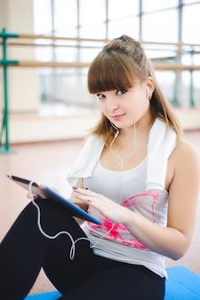 若い健康な女性は、フィットネスでタブレットコンピューターを使用します。
