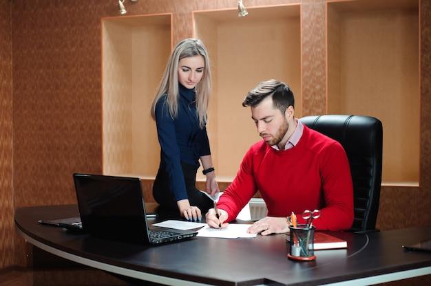 コンピューティングの前のテーブルに座っているビジネスパートナー。