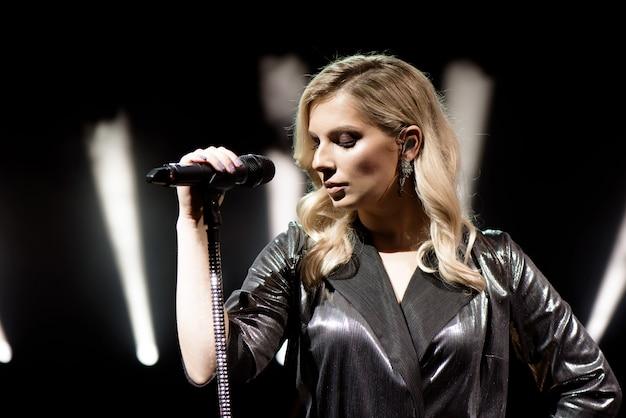 白い煙で歌っている若い美しい女性をクローズアップ。