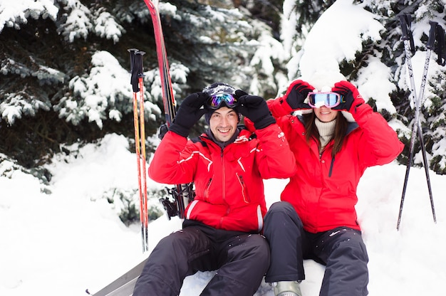 冬の森で一緒にスキーをする準備をして明るいジャケットを着た夫婦。