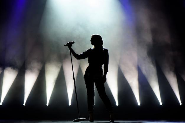 Вокалист поет в микрофон. певица в силуэте