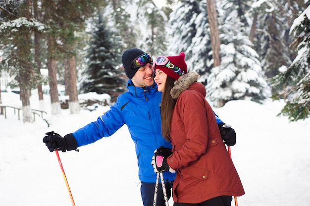 森のスキーリゾートでスキーをして幸せな夫婦