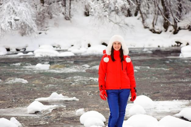 Молодая красивая девушка в зимнем лесу возле реки