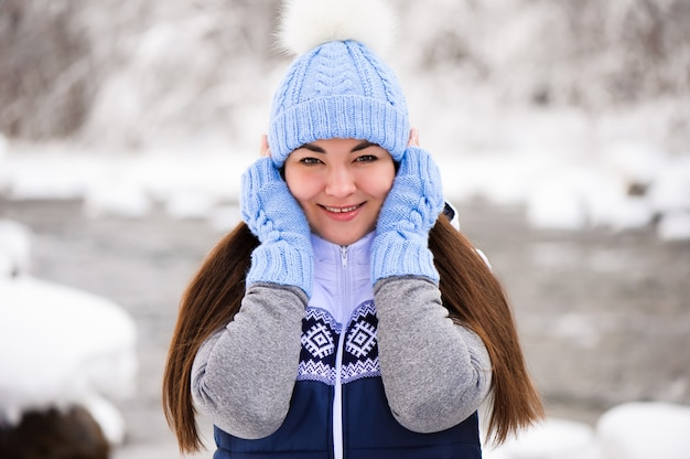 Красивая молодая женщина улыбается и играет со снегом в зимний сезон
