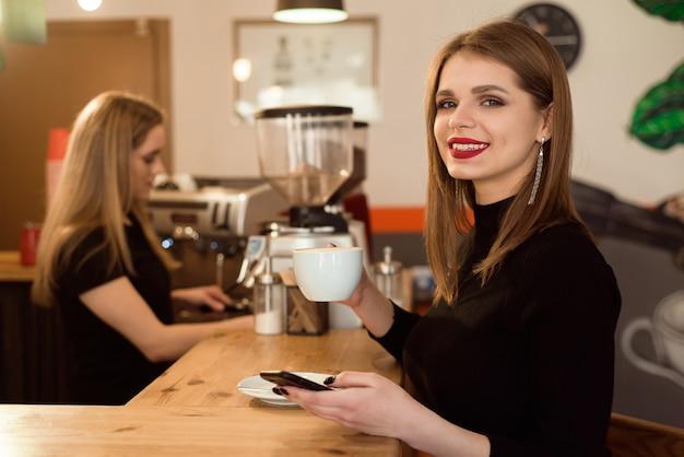 良い気分で笑顔の女性は、カフェに座ってコーヒーを楽しむ。