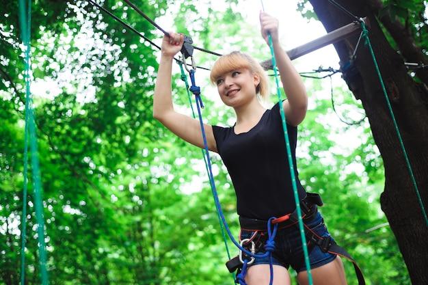 保険のためのベルトでロープ公園の若い女の子でハイキング。