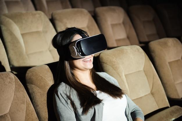 Молодая девушка с очки виртуальной реальности в мягком кресле.