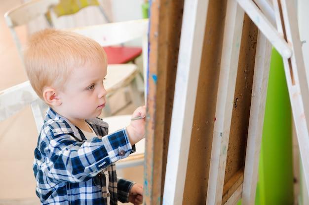 Ребенок рисует картину, рисует на уроке искусства