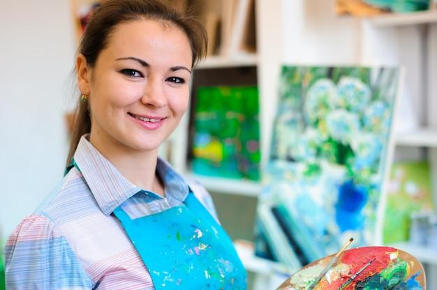 Красивая молодая девушка рисует картину красками на уроке искусства.