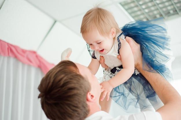 Папа обнимает и целует свою маленькую дочь.