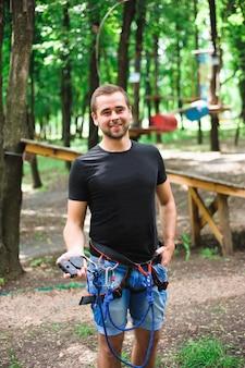 Поход в канатный парк молодого человека в безопасном снаряжении.