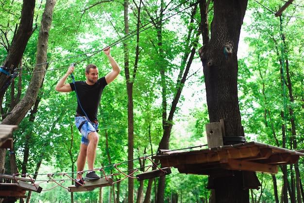 安全なギアでロープ公園の若い男でハイキング。