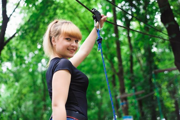 Поход в канатный парк молодая девушка в поясе для страхования.