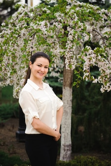 Девушка в весеннем парке возле цветущего дерева.