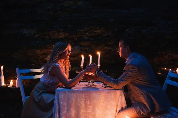 ろうそくの明かりで一緒に手を繋いでいるロマンチックなカップル