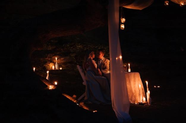 ろうそくの明かりで、屋外でロマンチックなディナーを楽しんでいる若いカップル
