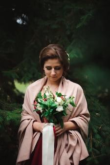 花束とウェディングドレスの若い美しい女性