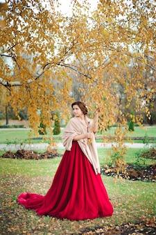 秋の森の赤いドレスを着た美しい少女