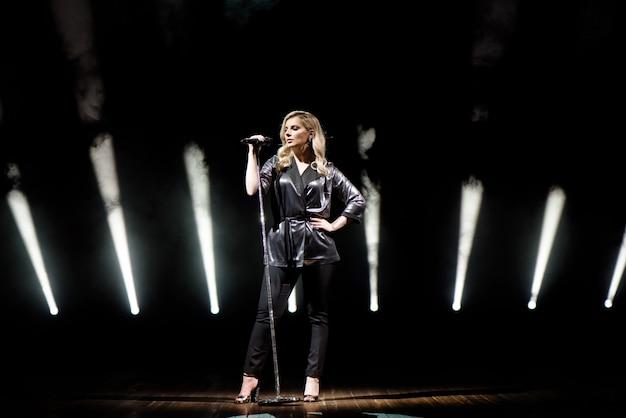 Женщина певица с длинными волосами держит микрофон с подставкой и поет.