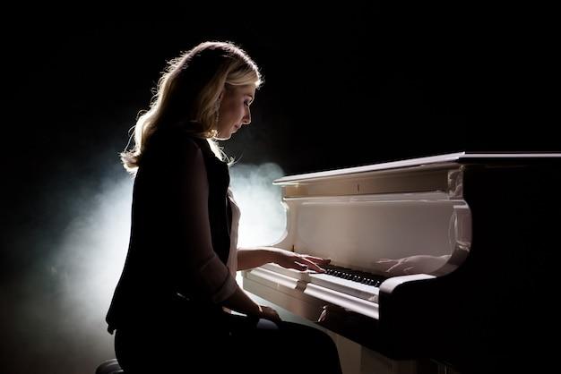 Пианист, музыкант, играет фортепианная музыка. музыкальный инструмент рояль с женщиной-исполнителем