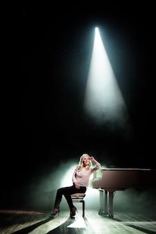 ステージ上の白いピアノに近いポーズのピアニスト