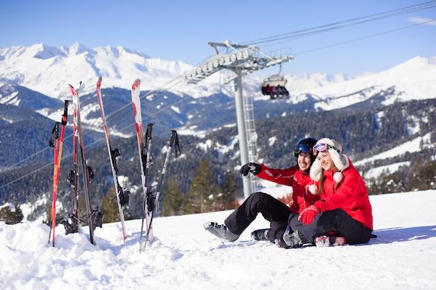 Влюбленная пара сидит на вершине горы и отдыхает вместе.