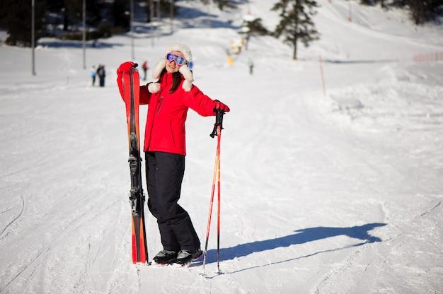山のふもとに彼女の手でスキーを持つ女性と冬の休日とスポーツコンセプト