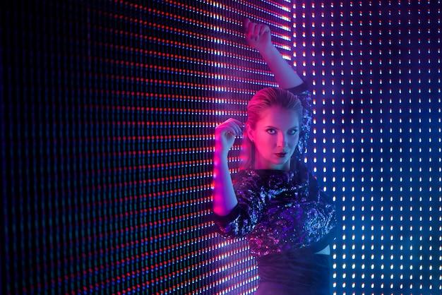 Танцор диско в неоновом свете в ночном клубе.