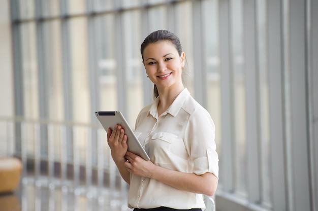 タブレットコンピューターの窓のそばに立っている若い実業家。
