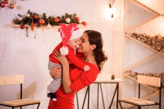 Счастливая мама и малыш в новогодней шапке празднуют рождество