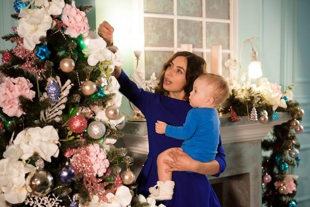 Милый мальчик и его мать украшения елки на праздник