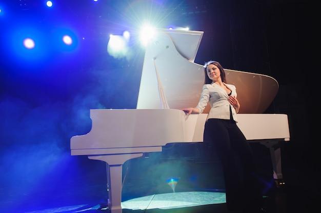 Женщина с белым роялем на сцене.