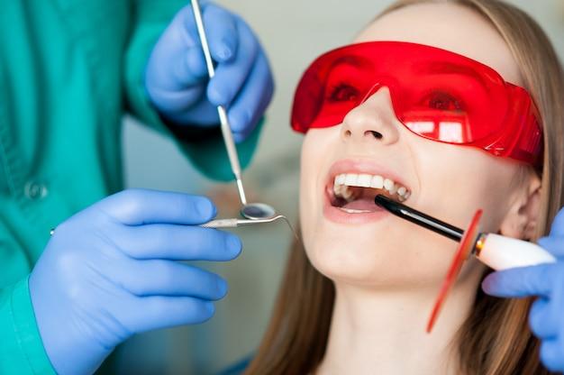 歯科医院で患者の歯を調べる。