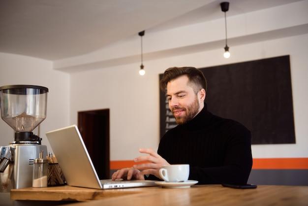 ビジネスの男性が喫茶店でコーヒーを飲んでいると彼のラップトップに取り組んでいます。