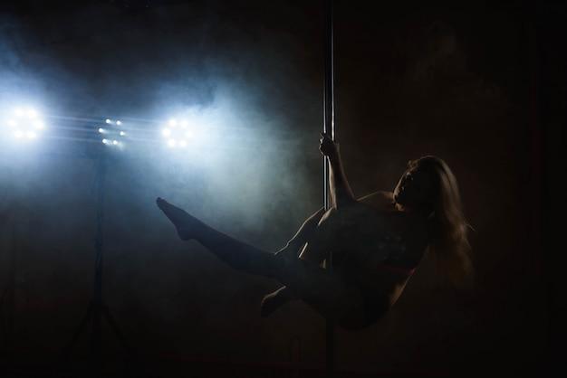 パイロンと美しいスリムな女の子。ポールで踊る女性ポールダンサーの女性