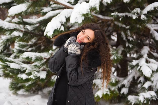 流行の服で妊娠中の女性の冬の屋外のポートレート