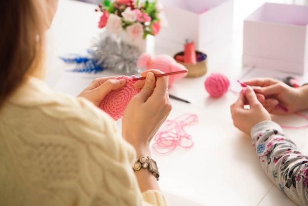 かぎ針編みのレッスンで若い魅力的な女の子