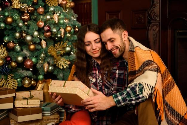 クリスマスツリーの近くの贈り物と若いカップル