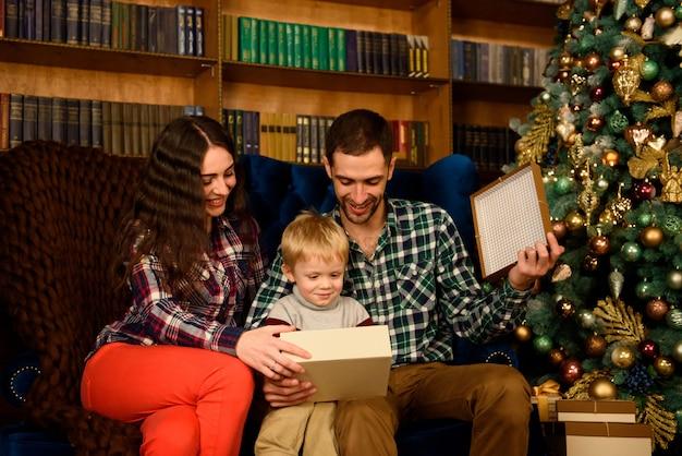 夜のクリスマスツリーのインテリアで魔法の光を探しているクリスマス家族オープンプレゼントギフトバッグ