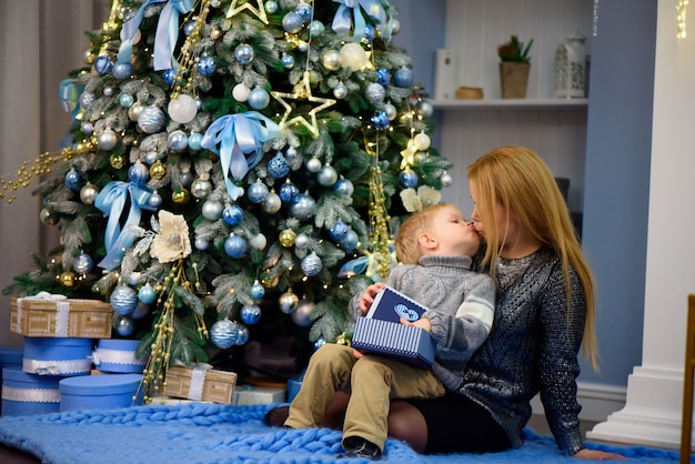 Счастливая семья, мать и ребенок маленький сын, играя дома на рождественские праздники. новогодние каникулы.